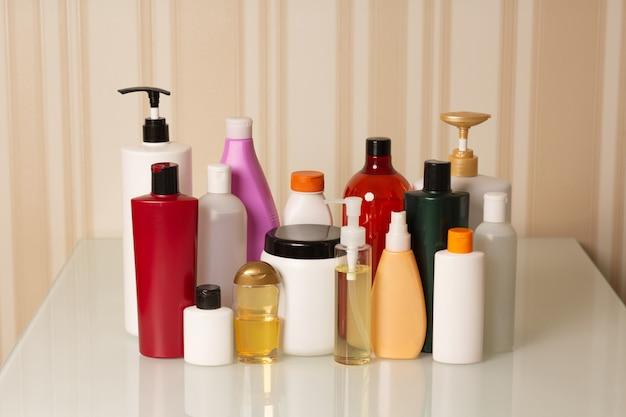ヘアケアおよびトリートメント製品:ベージュの背景にシャンプー、コンディショナー、マスク、オイル、美容液