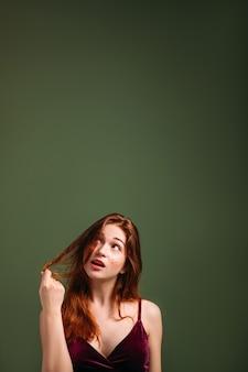 ヘアケアとトリートメント。仮想広告を見上げている若い赤毛の女性