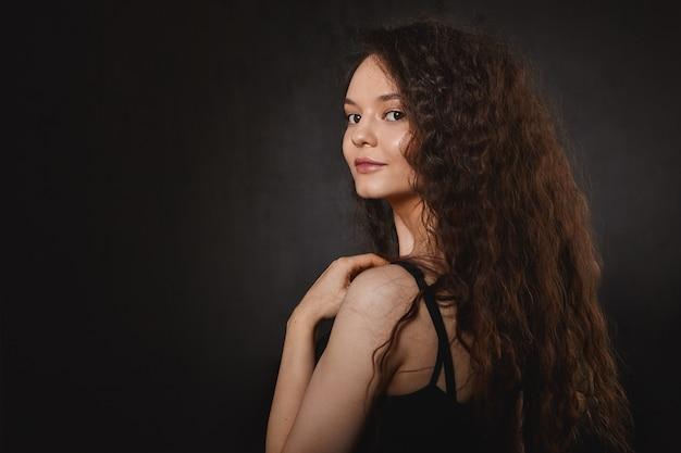 헤어 케어, 미용 및 패션 개념. 매력적인 미소와 긴 건강한 머리카락을 가진 놀라운 아름다운 젊은 갈색 머리 아가씨