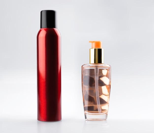 ヘアケア美容セット。ヘアスプレーの赤いアルミ缶と化粧品の血清エリキシルオイルが入った金色のディスペンサーガラス瓶。