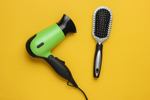 Hair care beauty studio shot hair dryer comb on yellow background