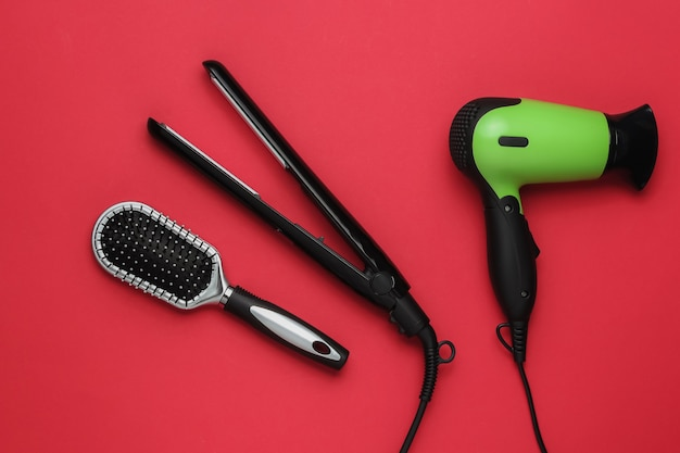 Hair care beauty studio shot hair dryer iron comb on red background top view