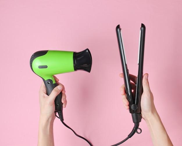 ヘアケア。ピンクのストレートヘアドライヤーとドライヤーを保持している女性の手。