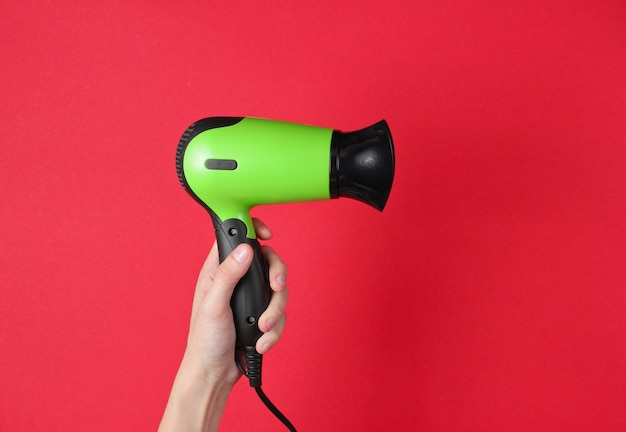Hair care. female hands holding hairdryer on red.