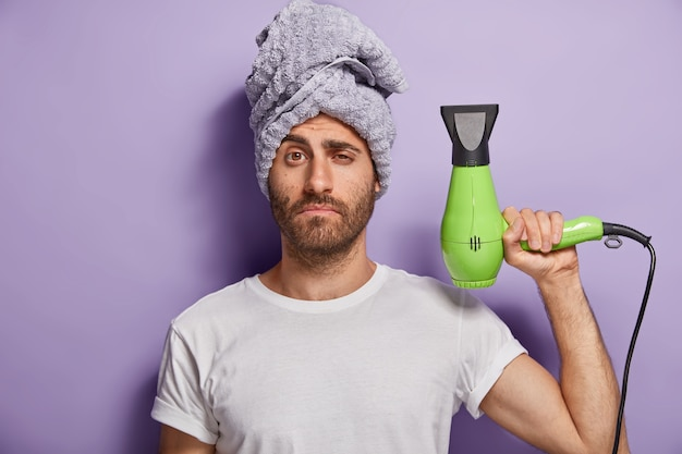 Hair care and grooming concept. sleepy man holds hairdryer, going to make hairstyle after taking shower, wears soft towel on head