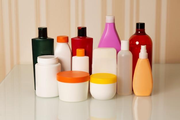 ヘアケア製品:ベージュの背景にシャンプー、コンディショナー、マスク、オイル、美容液