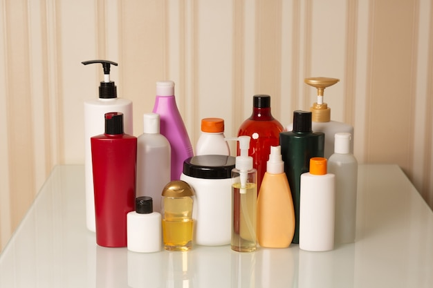 Hair care and treatment products: shampoo, conditioner, mask, oil and serum on a beige background
