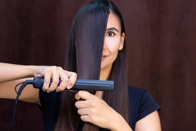 Hair care. a young woman has a curling iron in her hands to straighten her hair. keratin straightening
