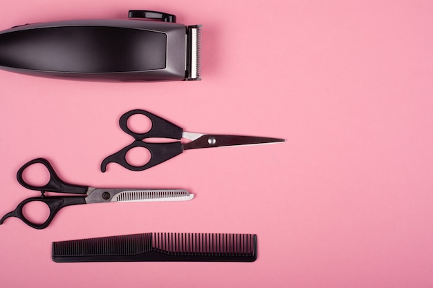 Hair clipper, straight and thinning barber scissors and comb on a pink background top view