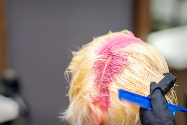 헤어 살롱에서 젊은 금발의 여자의 머리 뿌리에 핑크 색상의 헤어 컬러링