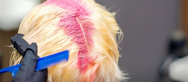 Hair coloring in pink color on hair roots of young blonde woman in hair salon. selective focus