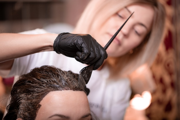 Hair coloring in the salon, hair styling. professional wizard paints the hair in the salon. beauty concept, hair care.