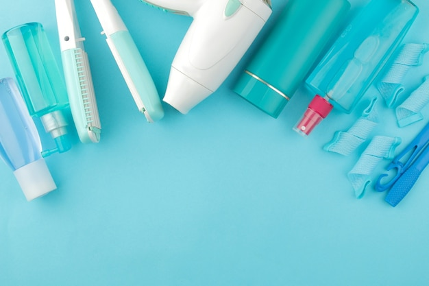 ヘアコスメティックスとヘアアクセサリー、ヘアカーラー、コーム、バレッタ、ゴムバンド。明るい青色の背景に。ヘアケア製品。テキスト用のスペースのある上面図