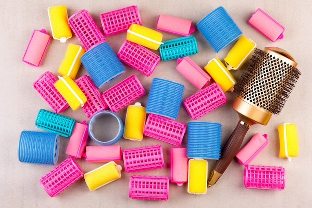 Hair curlers of different colors and the comb top view closeup