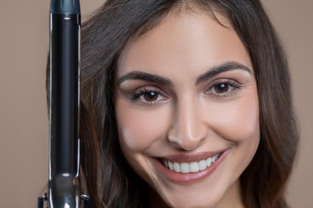 ヘアカールプロセス。ヘアアイロンで髪をしている白い歯の笑顔で幸せなきれいな女性の顔をクローズアップ