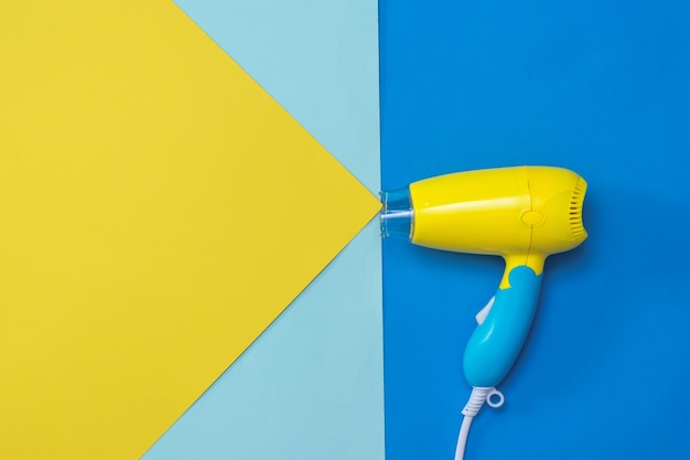 Hair dryer with white wire on colorful wall. devices for drying hair on a colorful wall.