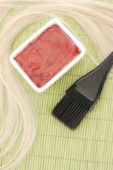 Hair dye in bowl and brush for hair coloring on green bamboo mat