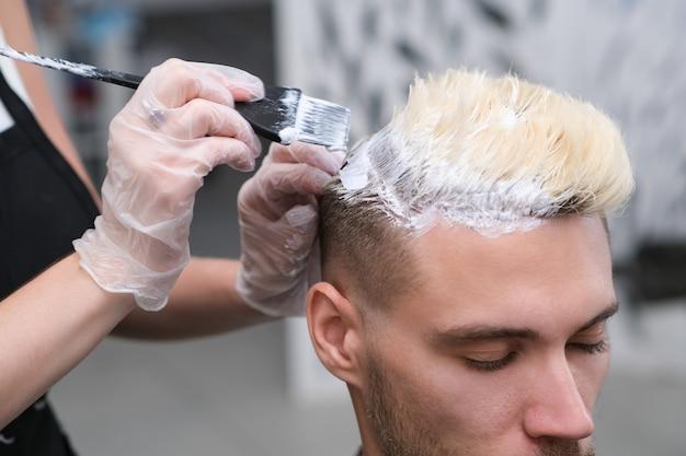 美容院で若い男性のための染毛。マスターはクライアントの髪をブリーチします