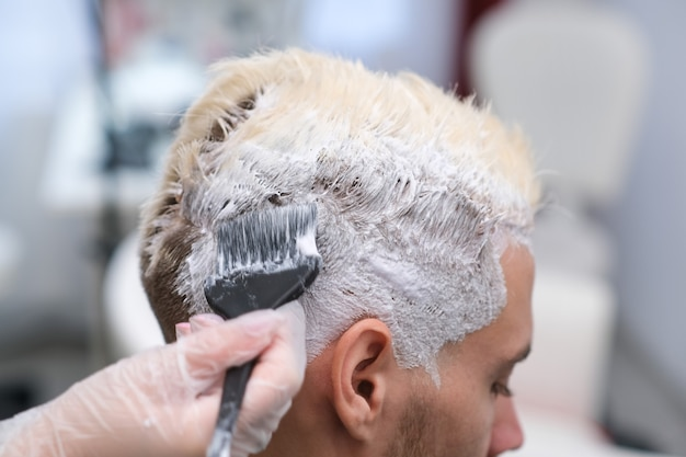 Hair dyeing for a young man in a hairdressing salon. the master bleaches the hair of the client