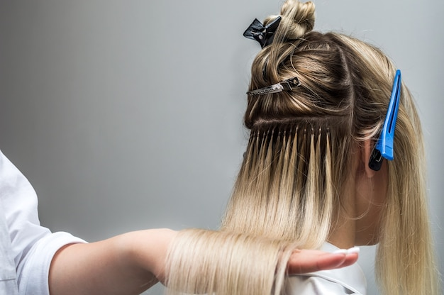 Hair extensions to a client close up in a beauty salon