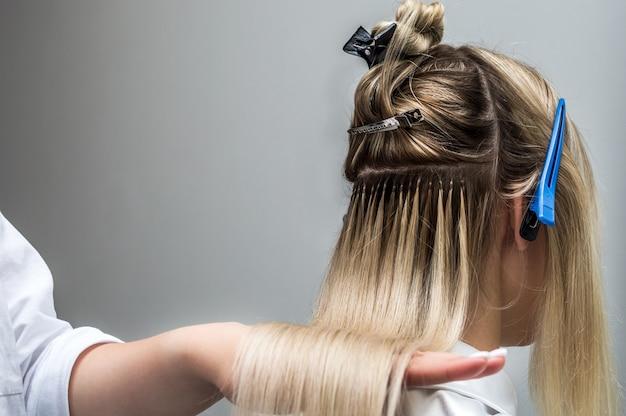 Наращивание волос клиенту крупным планом в салоне красоты