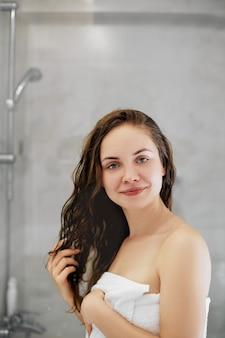 Волосы. девушка трогательно ее волосы и улыбается, глядя в зеркало. портрет счастливой молодой женщины с мокрыми волосами в ванной комнате. уход за волосами и кожей. девушка использует защитный увлажняющий крем.