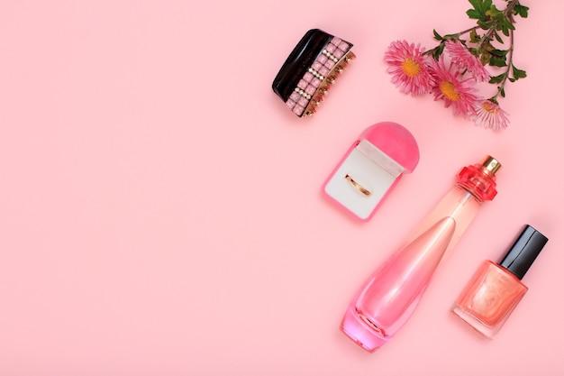 ヘアグリップ、金色のリングが付いたボックス、花、香水のボトル、ピンクの背景にマニキュアが入ったボトル。女性の化粧品とアクセサリー。コピースペースのある上面図。