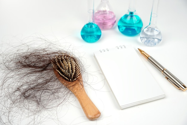 Hair loss comb blur background science test tubenotebookpen solve hair loss problems with science