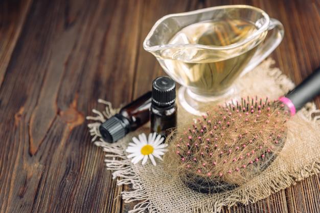 Потеря волос. расчешите волосы и эфирные масла, ромашки и витаминные капсулы на темном дереве.