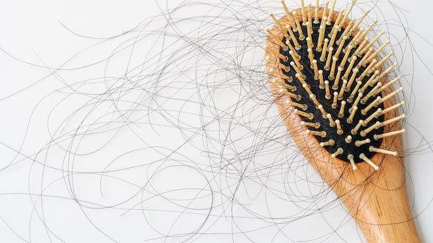 빗 머리의 탈모는 흰색 바탕에 매일 심각한 문제가 있습니다.