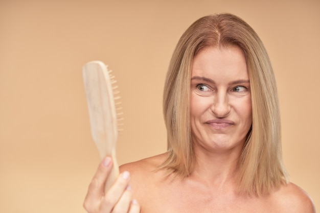 Hair loss problem frustrated and upset mature blonde woman looking at comb