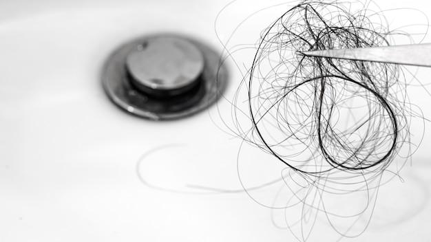 Проблема выпадения волос в белой раковине крупным планом