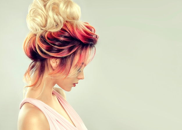 ヘアペインティング。色とりどりの髪を持つ若い魅力的な女性は、大きな金髪のお団子とエレガントな夜の髪型に集まりました。理髪と髪の色付け