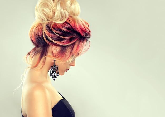 ヘアペインティング。色とりどりの髪を持つ若い魅力的な女性は、大きな金髪のお団子とエレガントな夜の髪型に集まりました。理髪アートと髪の色。