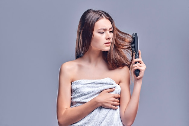 머리 문제 - 불행한 젊은 여성이 회색 배경에 격리된 머리를 빗고 있습니다. 탈모, 탈모.