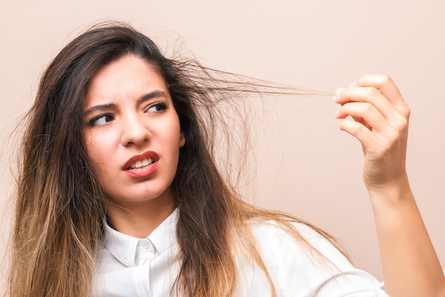 Hair problems. young woman in white shirt checking her britle, damaged, and split hairs against pink background