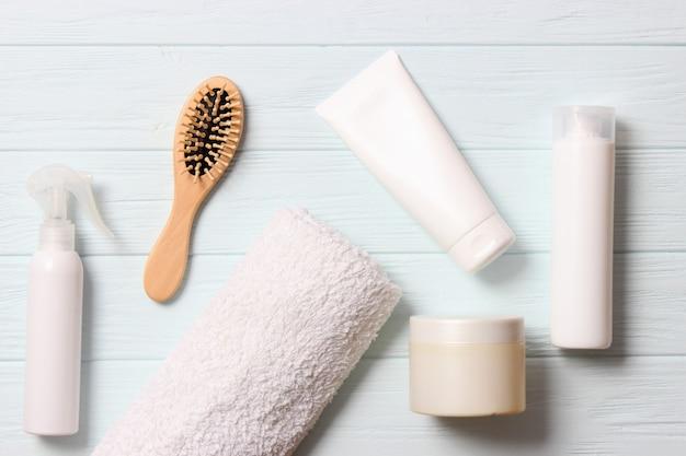 Продукты для волос и расческа на цветном фоне крупным планом