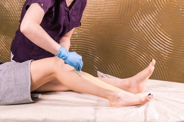 スパ高級店での脱毛。女性の脚は砂糖でワックスをかけます。ホットシュガー。