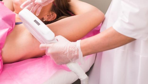 미용 미용 스파 클리닉의 치료사의 제모 미용 절차. 레이저 제모. 미용 및 spa 개념입니다.