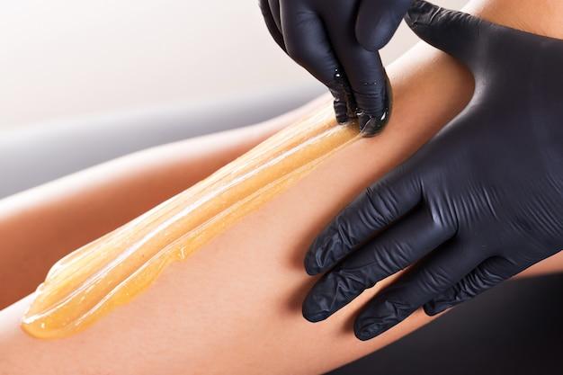 Процесс удаления волос на женской ноге с эпиляцией