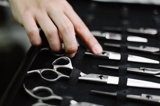 헤어 살롱 컨셉은 다양한 크기의 스테인리스로 만들어진 가위 컬렉션을 특정 가죽 케이스에 보관합니다.