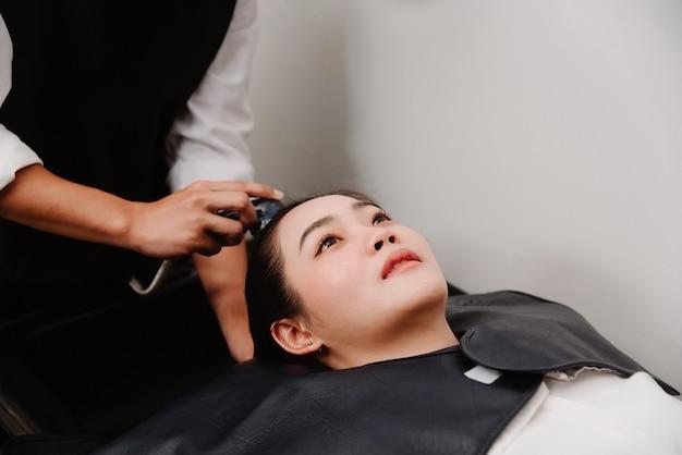Концепция парикмахерской мужской парикмахер, держащий душ с водой, нежно моет клиентку