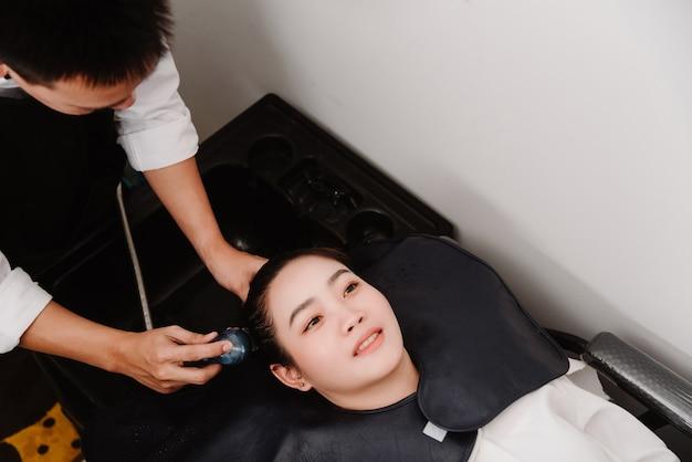 ヘアサロンのコンセプトは、ウォーターシャワーを持っている男性の美容師が女性の顧客の髪を優しく洗うことです。