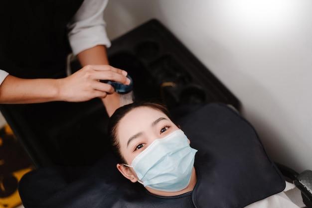 Концепция парикмахерской: парикмахер-мужчина, принимающий водный душ, осторожно моет волосы клиентке.