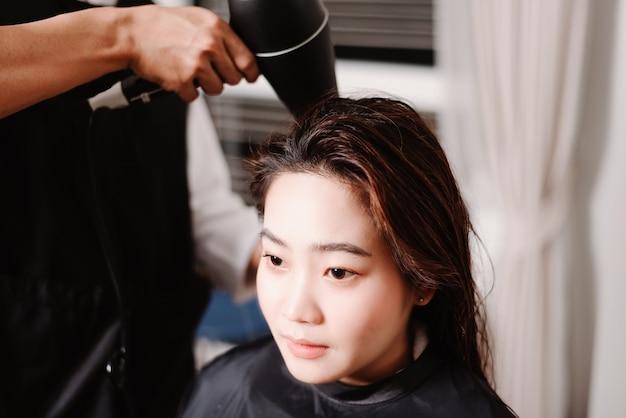 ヘアサロンのコンセプトは、ヘアドライヤーを使用して、ヘアウォッシュプロセス後に女性のお客様の濡れた髪を乾燥させる男性の美容師です。