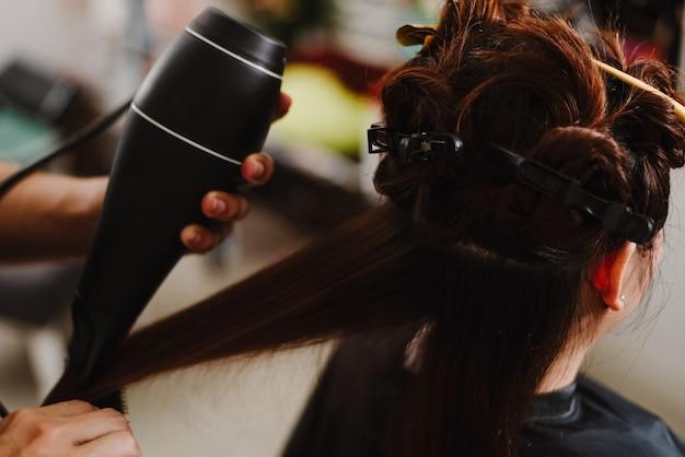 헤어 살롱 개념 남성 헤어스타일리스트는 빗을 사용하여 머리카락을 잡고 헤어드라이어를 사용하여 건조 및 스트레이트닝