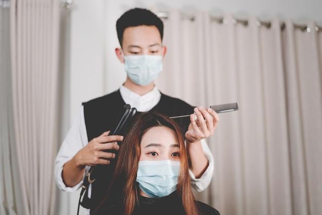 男性のヘアスタイリストと女性の顧客の両方がヘアカットプロセス中に保護フェイスマスクを着用するヘアサロンのコンセプト。