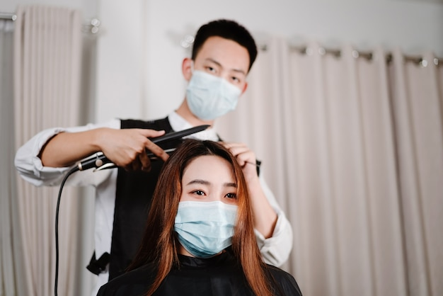 Концепция парикмахерской как мужской парикмахер, так и женщина-клиентка в защитных масках во время стрижки.