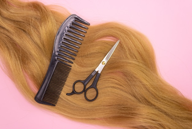 Волосы, ножницы и расческа на розовом фоне, вид сверху. парикмахерская, уход за волосами.