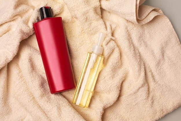 バスルームのしわくちゃのタオルの上に横たわるヘアシャンプーとクリーニングオイル。コピースペース